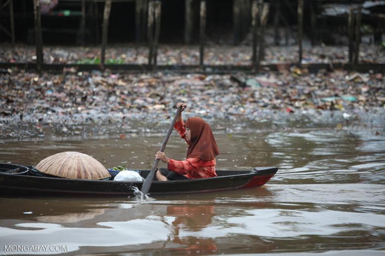 Woman paddling a canoe in Banjarmasin