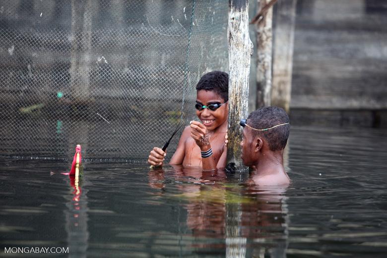 Kids fixing a fishing new in Lake Sentani
