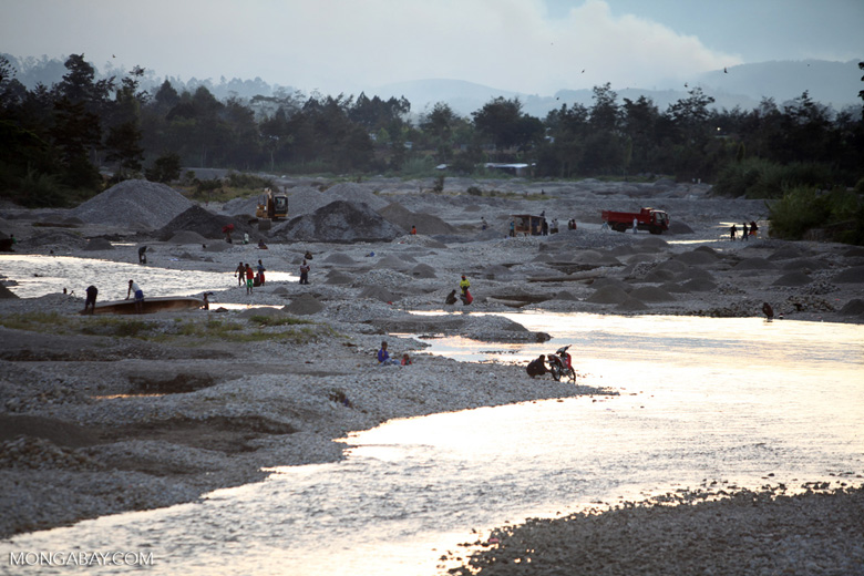 Papuans washing their laundry and rock mining in a highland river