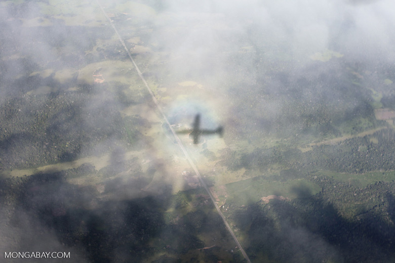 Aerial view of a shadow of a plane in the clouds over the Peruvian Amazon