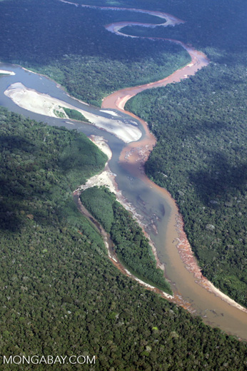 River polluted with mine tailings entering a rainforest river in Peru