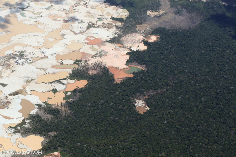 Airplane view of Amazon rainforest landscape scarred by open pit gold mining