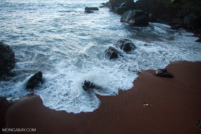 Waves crashing on a red sand beach