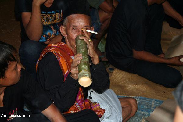 Old man drinking rice wine at funeral (Toraja Land (Torajaland), Sulawesi)