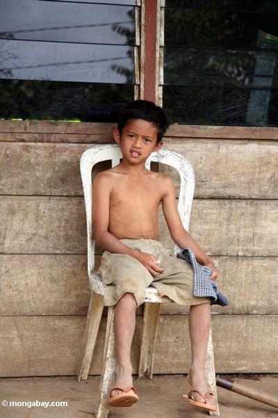 Boy on porch in Tikala (Toraja Land (Torajaland), Sulawesi)