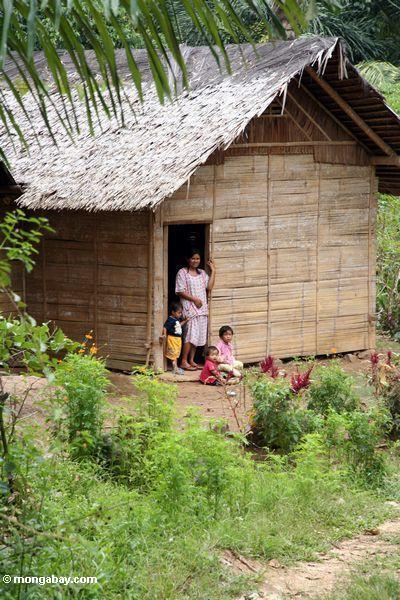 Mother and children in doorway of house near Tikala (Toraja Land (Torajaland), Sulawesi)