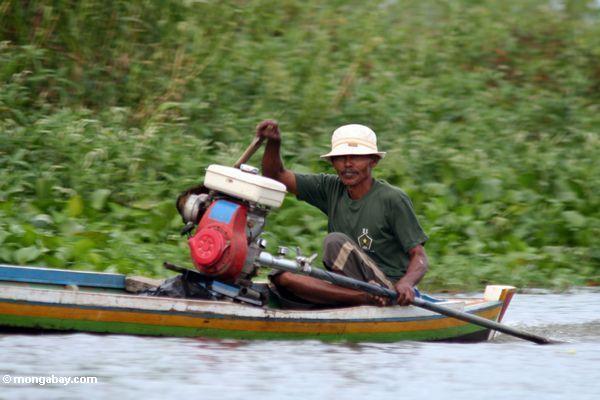 Man driving traditional Buginese motorized canoe (Sulawesi - Celebes) -- sulawesi7671