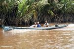 Men in long boat on the Seikonyer River (Kalimantan, Borneo - Indonesian Borneo)