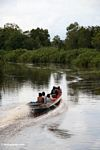 Family headed upriver in boat with outboard motor (Kalimantan, Borneo - Indonesian Borneo)
