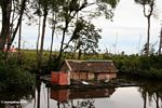 Floating house on the Seikonyer River, with cleared forest area in the background (Kalimantan, Borneo - Indonesian Borneo)