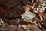 Rupiah note among cigarettes and coins at grave site in cave at Londa (Toraja Land (Torajaland), Sulawesi)