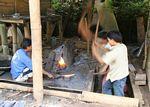 Metal workers hammering a machete into shape (Toraja Land (Torajaland), Sulawesi)