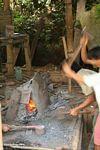 Metal workers pounding a hand knife into shape (Toraja Land (Torajaland), Sulawesi)