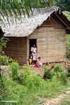 Mother and children in doorway of house near Tikala (Toraja Land (Torajaland), Sulawesi)
