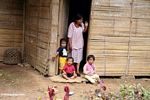 Mother with kids in doorway of home near Tikala (Toraja Land (Torajaland), Sulawesi)