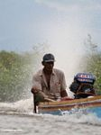 Man driving traditional Buginese motorized canoe (Sulawesi - Celebes)